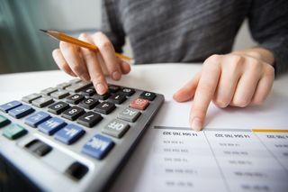 ręce na stole z kalkulatorem i dokumentami